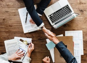 business people shaking hands over table
