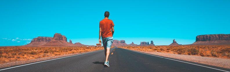 Young man walking down road